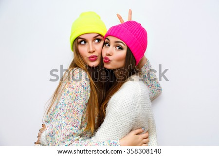 Cute positive portrait of best friend pretty young girls, winter time, neon hats, cozy sweaters, hugs and having fun, natural glowing makeup, two sisters sending air kiss, joy, couple, emotions. - stock photo