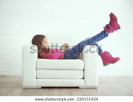 Cute pre-teen girl wearing fashion winter clothes posing in white interior - stock photo