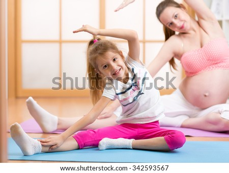 Cute pregnant mother and child daughter doing exercise at home