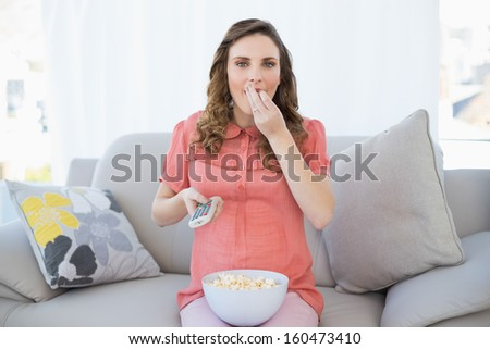 Cute pregnant woman eating popcorn while watching television in the living room - stock photo