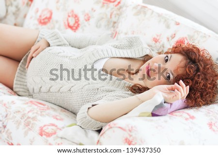 Cute pregnant woman touching her belly while lying on a bed at home - stock photo