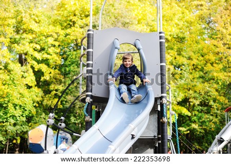 Cute prescholler boy excitedly plays on a grey playground slide on a cool sunny autumn day