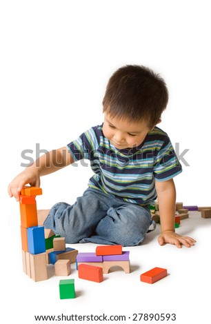 Cute preschool boy concentrating, playing with wooden blocks. Isolated studio shot on white.