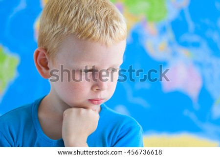 Cute preschool boy dreaming in front of  world map - stock photo