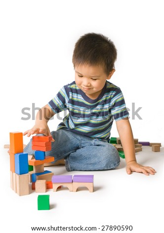 Cute preschool boy having fun playing with wooden blocks. Isolated studio shot on white.