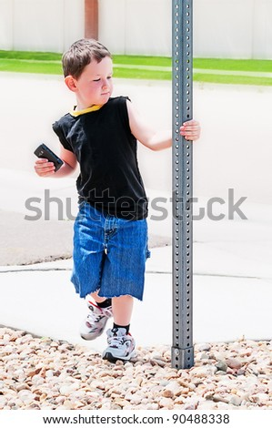 Cute preschool boy playing around a street sign while holding a cellphone in his hand. - stock photo