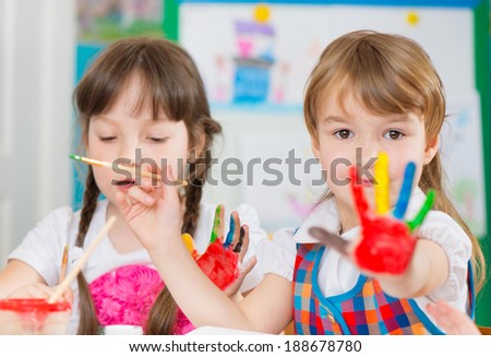 Cute preschool children painting with their palms at kindergarten