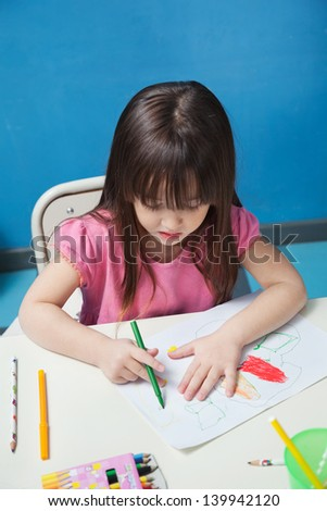 Cute preschool girl drawing with sketch pen at desk in classroom - stock photo