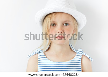 Cute preschool girl with green eyes and blonde hair wearing striped dress and white hat looking at the camera while posing against white studio wall background. Pretty serious little female model - stock photo