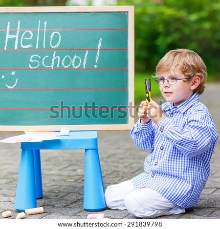 Cute preschool kid boy with glasses at blackboard practicing writing, outdoor. school or nursery. Back to school concept - stock photo
