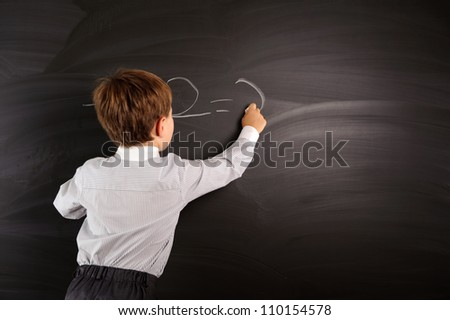 Cute preschooler against dark blackboard in classroom