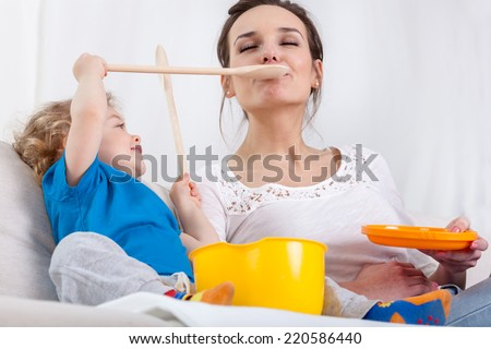 Cute preschooler and mum playing at kitchen - stock photo