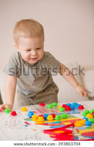 Cute preschooler child boy plays with mosaic at home. A blond little toddler playing in kid's room. Leisure activities. indoors. Boy sorting colorful children's plastic blocks. Development, education
