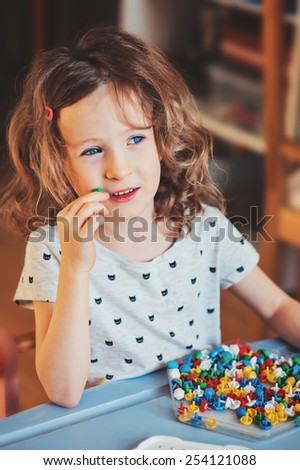 cute preschooler child girl plays with colorful mosaic at home - stock photo