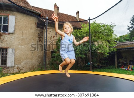 Cute preschooler girl jumping on trampoline, childhood concept - stock photo