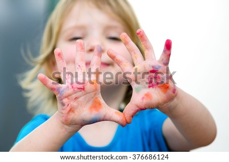 Cute preschooler girl with smile showing colored hands. Selective focus on palms. - stock photo