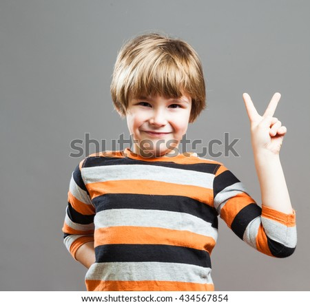 Cute Preschooler having fun in orange black striped shirt, making a Peace Sign with his Fingers - stock photo