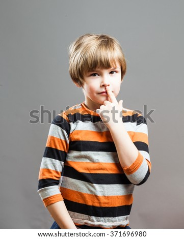 Cute Preschooler having fun in orange black striped shirt, touching his nose with finger - stock photo
