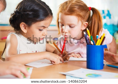 Cute preschoolers drawing with colorful pencils at daycare - stock photo