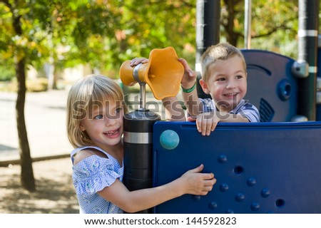 Cute preschoolers playing at the playground.