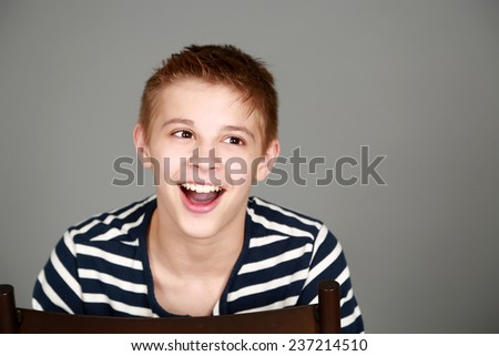 cute preteen blond boy smiling and looking to side - stock photo