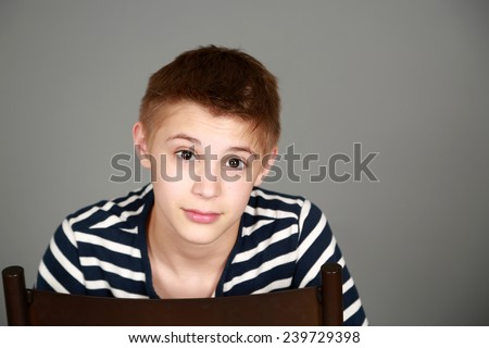 cute preteen blond boy with eyebrows raised - stock photo