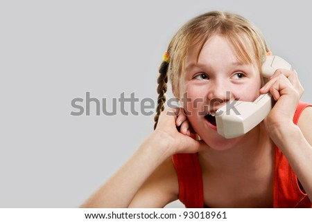 Cute preteen girl talking by phone receiver - stock photo