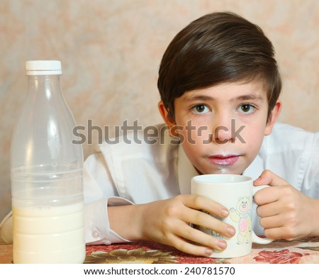 cute preteen handsome boy drink milk from mug - stock photo