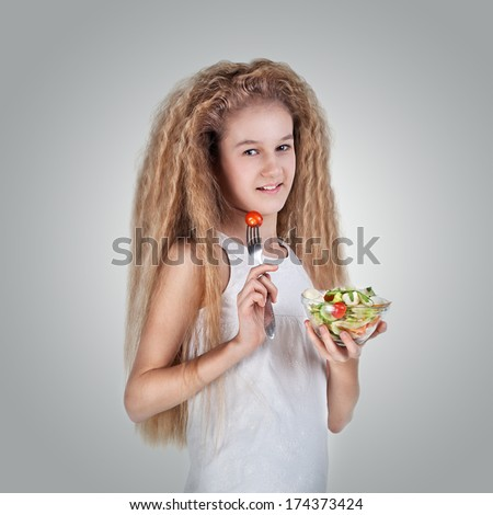 Cute pretty beautiful happy little girl with long hair eating vegetable salad, using fork - healthy food concept