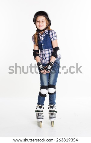 Cute pretty child girl having fun in roller skates on a white background, studio shoot - stock photo