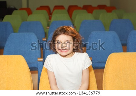 cute pretty emotional little girl in the cinema hall