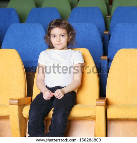 cute pretty emotional little girl in the cinema hall - stock photo