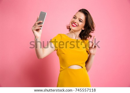 Cute pretty girl with bright makeup showing peace gesture while taking selfie on mobile phone, isolated over pink background