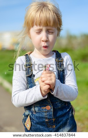 Cute pretty little blond girl preparing to blow a dandelion clock standing with her mouth open ready to puff - stock photo