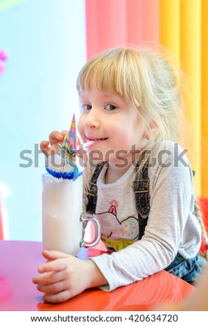 Cute pretty little blond girl standing at a table enjoying a milkshake treat licking her lips in pleasure - stock photo