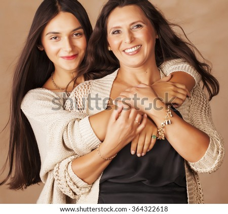 cute pretty teen daughter with mature mother hugging, fashion style brunette makeup close up tann mulattos, warm colors