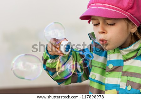 Cute pretty young girl blowing soap bubbles - stock photo