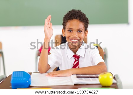 cute primary schoolboy hand up in classroom