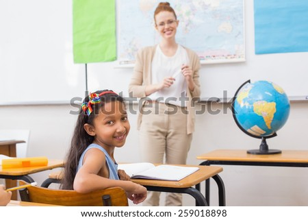 Cute pupil and teacher in classroom with globe at the elementary school - stock photo