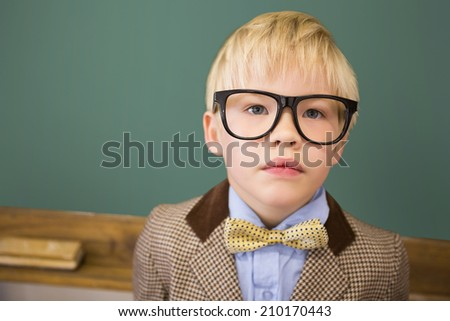 Cute pupil dressed up as teacher in classroom at the elementary school