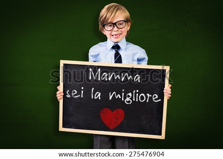 Cute pupil holding chalkboard against green - stock photo