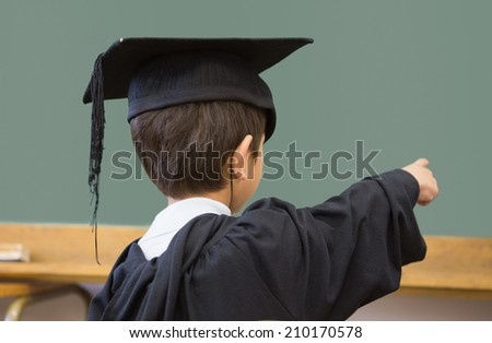 Cute pupil in graduation robe pointing in classroom at the elementary school - stock photo
