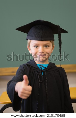 Cute pupil in mortar board smiling at camera in classroom at the elementary school