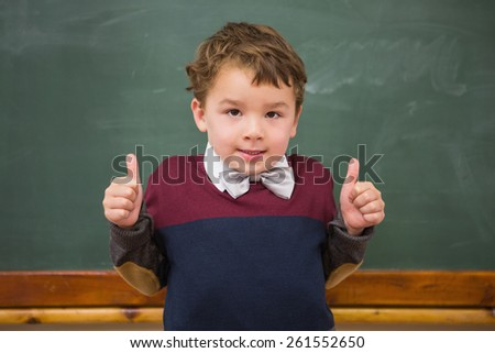 Cute pupil looking at camera with thumbs up at elementary school - stock photo