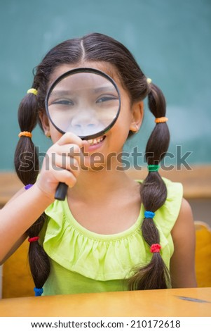 Cute pupil looking through magnifying glass in classroom at the elementary school - stock photo
