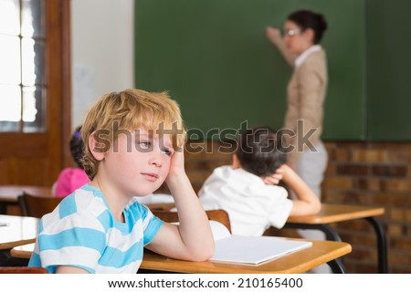 Cute pupil not paying attention in classroom at the elementary school