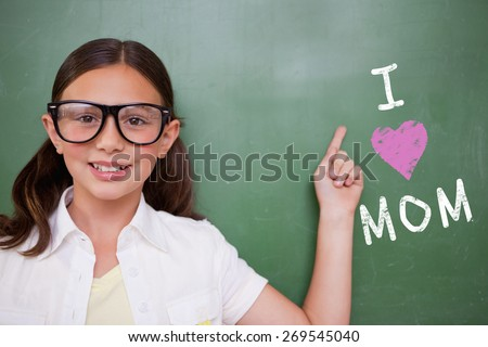 Cute pupil pointing against green chalkboard - stock photo