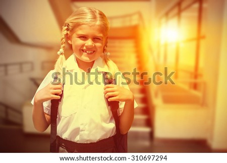 Cute pupil smiling at camera by the school bus against empty stair way - stock photo