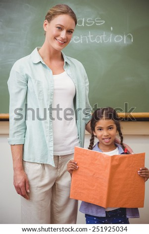 Cute pupil smiling at camera during class presentation at the elementary school - stock photo