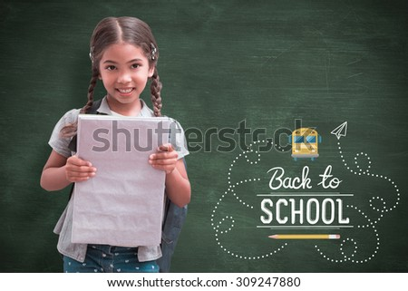 Cute pupil smiling at camera holding notepad against green chalkboard